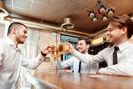Relaxing after hard working day. Three happy young men in shirt and tie holding glasses with beer and toasting while sitting at the bar counter photo