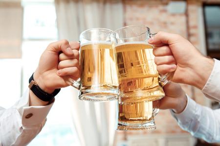 hombre tomando cerveza: Saludos. Primer plano de tres tazas con cerveza extendi� por hombres de negocios en el pub Foto de archivo