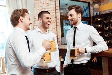 Having a pint with friends. Three cheerful young men in shirt and tie toasting with beer while standing together by the bar counter photo