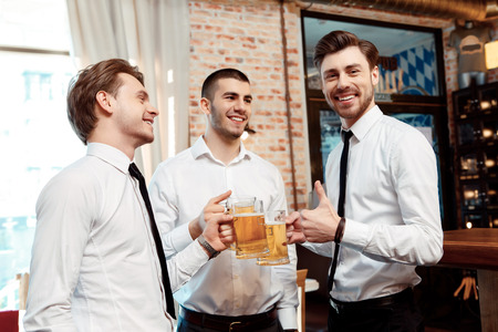Best company for the Friday night party. Four friends businessmen drink beer and rejoice together at the bar photo