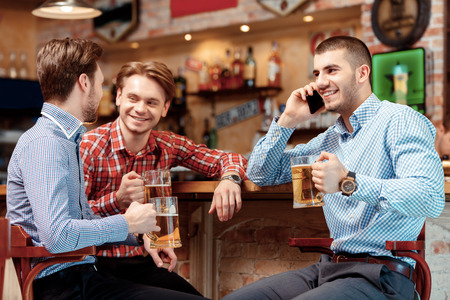 important phone call: Important call during meeting with friends. Three young men sitting at the bar counter and drinking beer while one of them talks over the phone