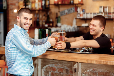 quench: Quench your thirst. Handsome young male bartender stretching out glasses with beer and smiling while standing at the bar counter
