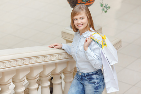 upstairs: Ready for shopping time. Attractive young girl in casualwear raising upstairs and carrying shopping bags
