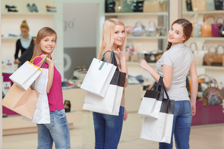 promotion girl: Never stop doing shopping. Three beautiful girls in casual clothes turning back to the camera while holding shopping bags copyspace at the store