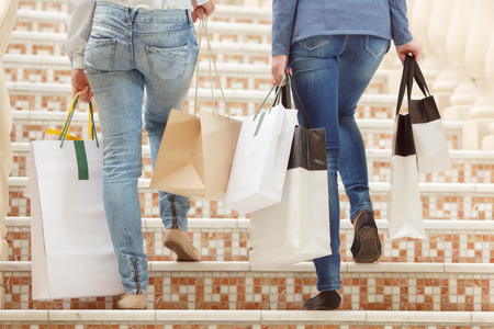 upstairs: Passionate shoppers. Close up of female legs going upstairs with numerous shopping bags copy space