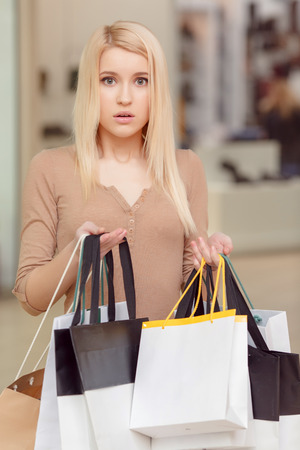 gift spending: Puzzled with the thought. Vertical shot of an attractive blond woman with the puzzled expression of her face holding shopping bags copyspace in her hands