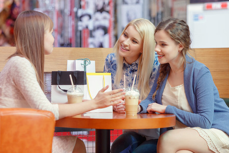 Warm friendly talk by the cocktail. Three charming young ladies having an exciting conversation sitting at the cafe in shopping mall photo