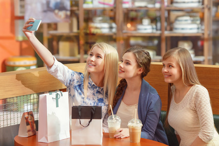 Best selfie for social media posting. Beautiful girls with shopping bags copy space taking a selfie with their cell phone photo