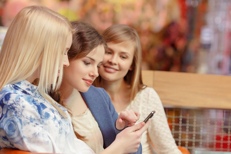 promotion girl: Looking through the pictures. Close-up of three beautiful young women looking at the screen of the smartphone