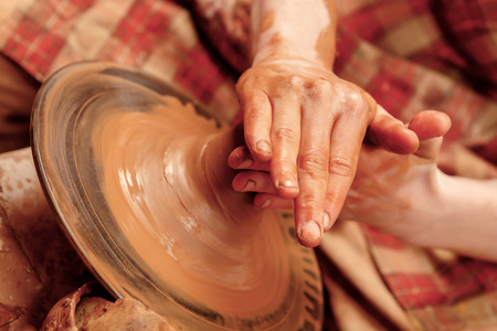 Creation of a clay pot. Close-up of hands of a teacher and a student working on pottery wheel and creating a clay pot photo