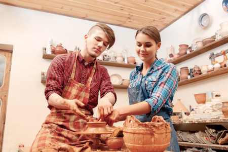 pottery: Mutual creative work. Young beautiful couple in casual clothes and aprons creating a bowl on a pottery wheel in a clay studio