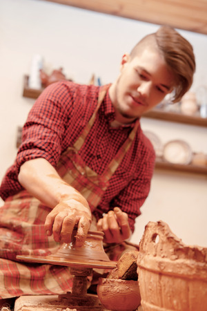 shaping: Clay modelling. Close-up of a young man in casual wear and apron shaping a clay pot in studio