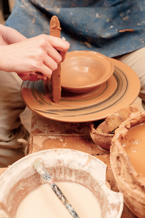 shaping: Creating a masterpiece. Artisan hands shaping clay with wooden jigger in clay studio