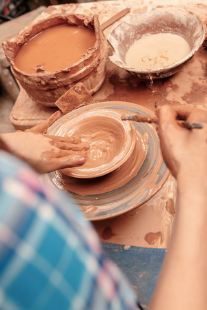 Creating a masterpiece. Artisan hands shaping clay with wooden jigger in clay studio photo