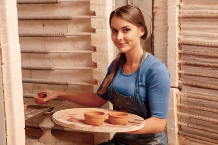 Clay jars created. Young smiling girl puts clay pots to the shelf so that they could get dry photo