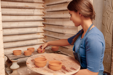 Beautiful home crockery. Young beautiful woman in apron holding a tray with clay pots on it putting them to the shelf photo
