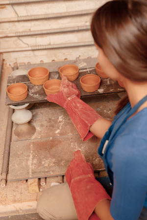 Pottery art. Close-up of a woman putting to the shelf just created earthen jars photo