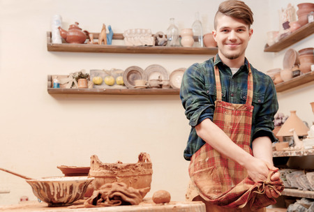 Cleaning up after work. Young cheerful potter cleaning his hands with his apron standing by the pottery wheel in clay studio Stock Photo