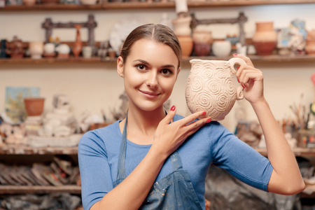 clay craft: Clay craft. Young and smiling female potter holding a jar on her shoulder