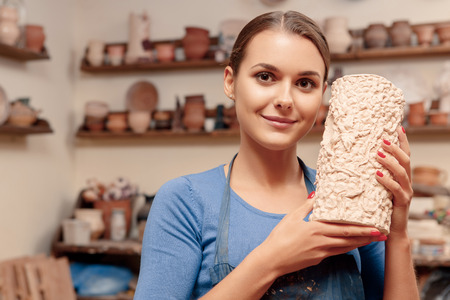 pottery: Pottery art. Young smiling girl in apron holding a clay vase in her hands standing in pottery studio