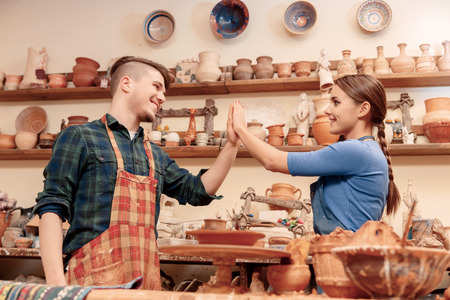 manual job: Great job. Two happy potters clap their hands being satisfied with their work in clay studio