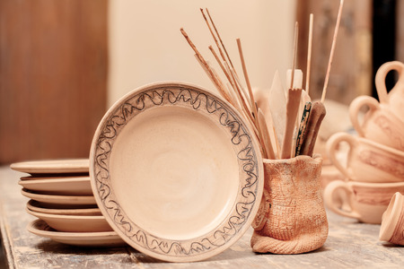 Ceramic masterpieces. Still life of ceramic plates with ornament and pot with pottery tools photo