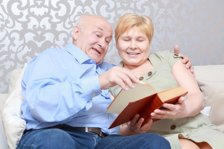 enjoyable: Enjoyable leisure. Cute senior couple looking through the book sitting on the couch at home