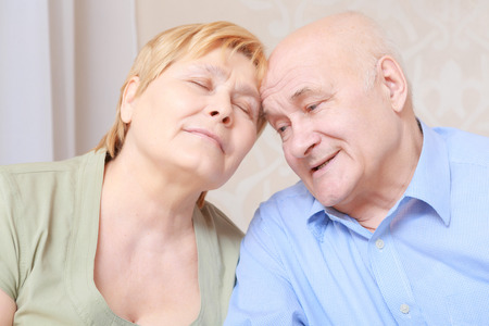 contentment: Happy together. Elderly couple share a tender moment of love as they sit close together with their eyes closed in contentment and bliss