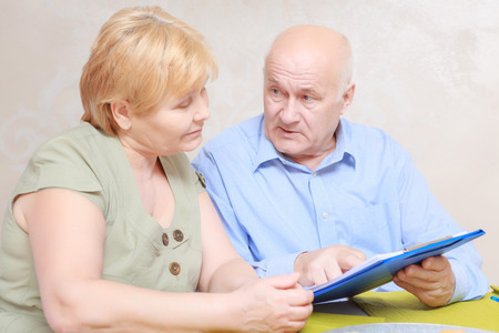 business communication: Communication on business issues. Elderly couple looking through the documents in a clipboard sitting in living room Stock Photo