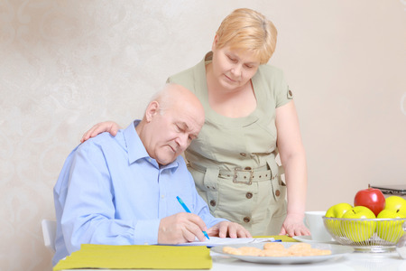 accountancy: Home accountancy. Elderly man and woman working with documents on a clipboard and tablet computer