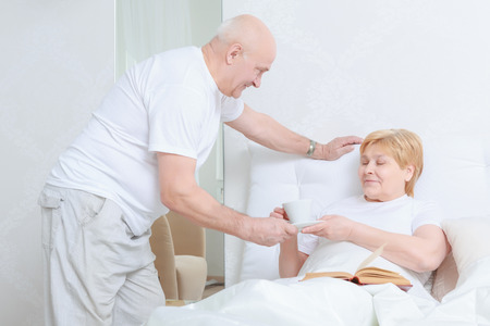 spouse: Caring after each other. Senior man bringing tea to his spouse lying in bed with a book