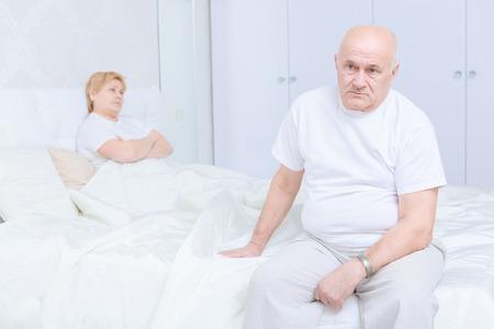decepci�n: Decepci�n. Hombre mayor triste que se sienta en la cama y mirando a otro lado con su esposa en el fondo Foto de archivo