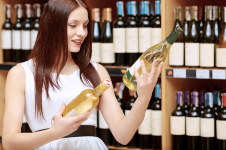 hesitation: Making choice. Young smiling woman with expression of hesitation comparing two bottles of wine in a liquor store Stock Photo