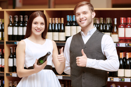 sommelier: Tasty wine for every occasion. Young smiling sommelier and beautiful woman holding a wine bottle and showing thumbs up standing in liquor store Stock Photo