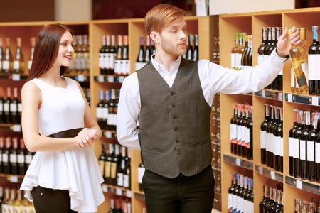 sommelier: Choosing the best wine for you. Cheerful young sommelier holding a wine bottle and pointing it