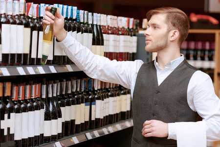 sommelier: Confident sommelier. Confident male sommelier holding wine bottle and smiling while standing near the wine shelf