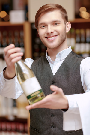 sommelier: Confident sommelier. Close-up of a handsome young sommelier holding a wine bottle and stretching it out to the camera
