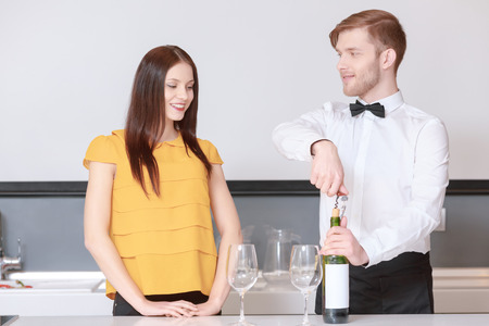 degustation: Wine degustation. Handsome sommelier with bow tie helping young attractive woman to choose wine at the degustation