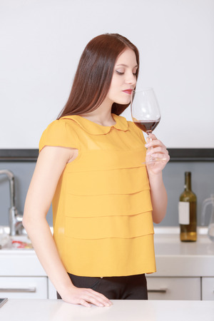 degustation: Wine degustation.  Portrait of a young woman sniffing wine at the degustation