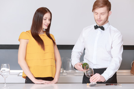 degustation: Wine degustation. Sommelier wearing a bow tie pouring wine to the glass and young attractive woman looking at this smiling Stock Photo