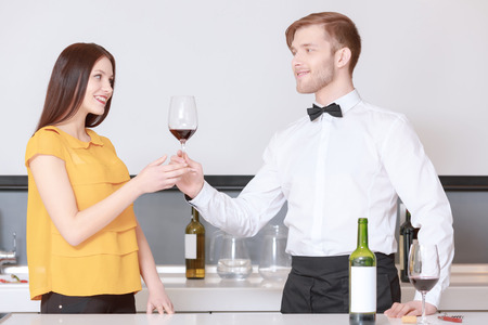 degustation: Taste of the best wine. Young handsome sommelier in a bow tie giving a glass with red wine to a beautiful woman at degustation Stock Photo