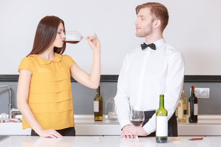 wine testing: Perfect grape taste. Young woman sipping red wine during wine testing process