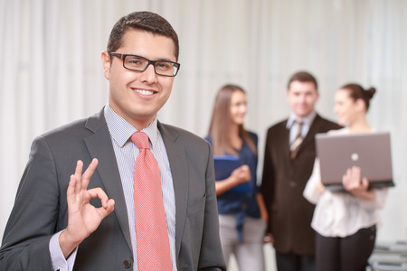 job satisfaction: Great job. Young handsome businessman wearing suit and tie showing ok sign smiling at a camera while his colleagues standing in blurry on the background Stock Photo
