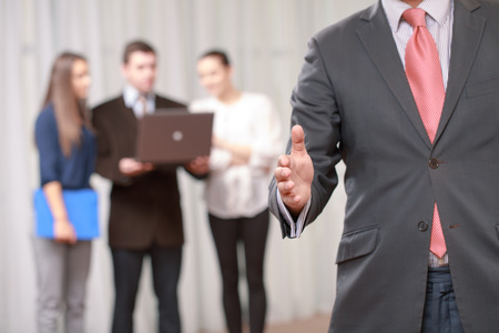 cropped out: Nice to meet you. Cropped view of a businessman stretching his hand out for a handshake at the meeting with a team on the background