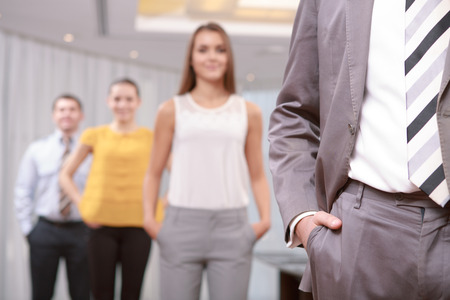 Dress code. Close-up of a business suit and a tie of a manager and business staff standing in blurry with their hands in pockets of the trousers