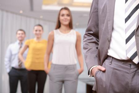 Dress code. Zbliżenie garnitur i krawat kierownika i pracowników stojących w rozmyte z rękami w kieszeniach spodni