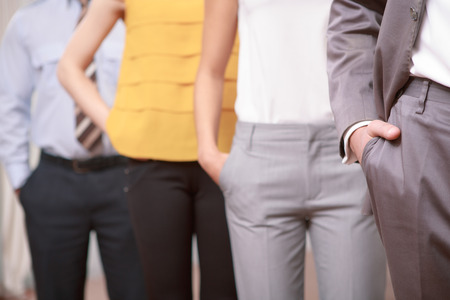 We are the team. Cropped shot of managers standing in a row with their hands in pockets of the trousers Stock Photo