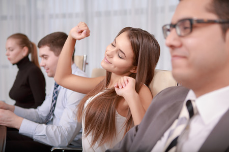 gracious: Time to rest. Young gracious female business manager stretching with a smile at the meeting with her colleagues Stock Photo