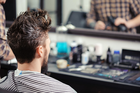 hairdressers: Close-up of a young man with his hair raised upwards sitting before the mirror at barbershop Stock Photo