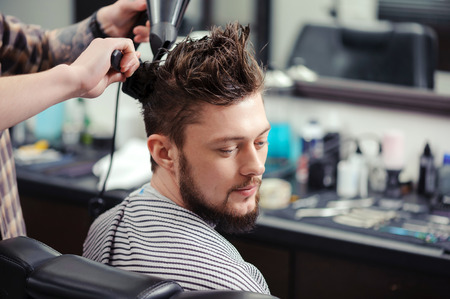 hairdressers shop: Hairstyling process. Close-up of a barber drying hair of a young bearded man